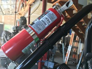 Refillable fire extinguisher mounted with TKO clamps